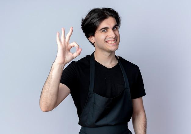 Uśmiechnięty młody przystojny mężczyzna fryzjer w mundurze pokazując okey gest na białym tle na białej ścianie