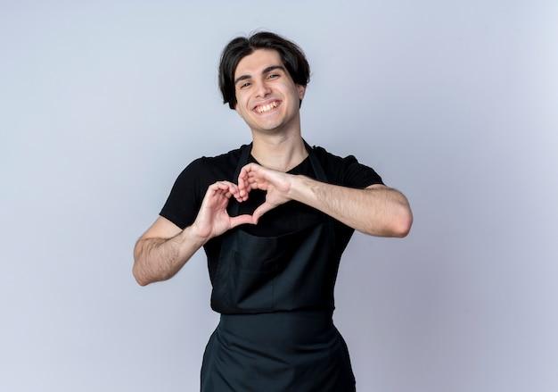 Uśmiechnięty młody przystojny mężczyzna fryzjer w mundurze pokazuje gest serca na białym tle