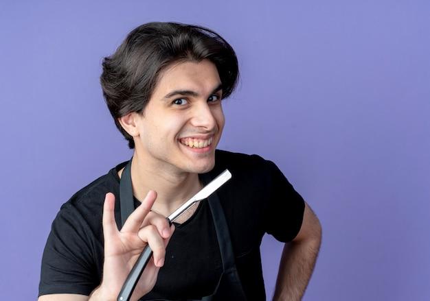 Uśmiechnięty młody przystojny mężczyzna fryzjer w mundurze trzyma prosto brzytwę na aparat odizolowany na niebiesko