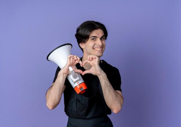 Uśmiechnięty młody przystojny mężczyzna fryzjer w mundurze trzymając głośnik i pokazując gest serca na niebieskim tle
