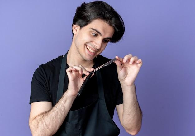 Uśmiechnięty młody przystojny mężczyzna fryzjer w mundurze trzymając i patrząc na brzytwę na niebiesko