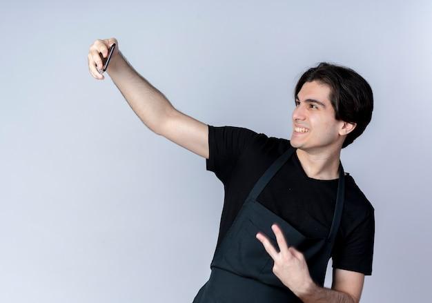 Uśmiechnięty młody przystojny mężczyzna fryzjer w mundurze weź selfie i pokazując gest pokoju na białym tle