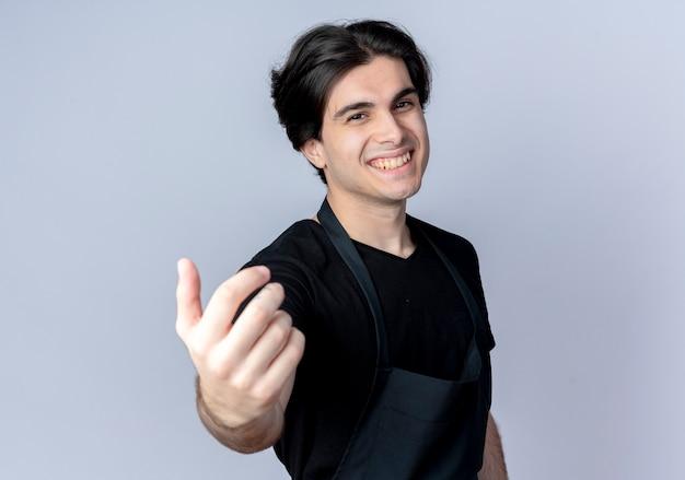 Uśmiechnięty młody przystojny mężczyzna fryzjer w mundurze wyciągając rękę na aparat na białym tle