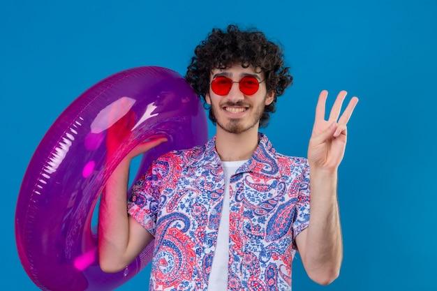Uśmiechnięty młody przystojny mężczyzna kręcone noszenie okularów przeciwsłonecznych trzymając pierścień pływacki pokazujący trzy na odosobnionej niebieskiej ścianie
