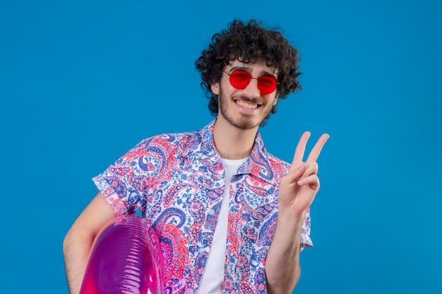 Uśmiechnięty młody przystojny mężczyzna kręcone w okularach przeciwsłonecznych trzyma pierścień pływacki robi znak pokoju na odosobnionej niebieskiej ścianie z miejsca na kopię