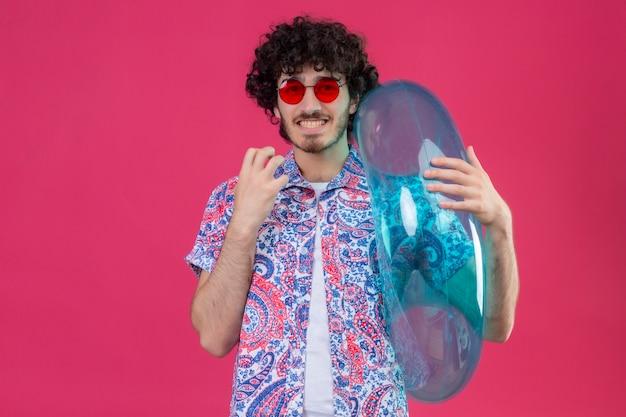 Uśmiechnięty młody przystojny mężczyzna kręcone w okularach przeciwsłonecznych, trzymając pierścień do pływania z podniesioną ręką na na białym tle różowej ścianie z miejsca na kopię