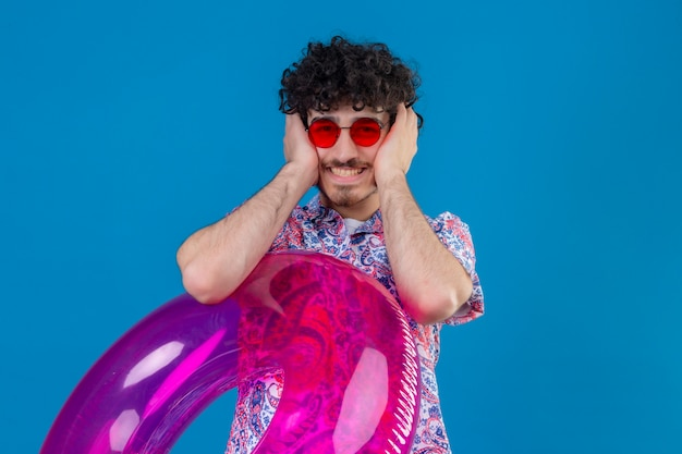 Uśmiechnięty młody przystojny mężczyzna kręcone w okularach przeciwsłonecznych trzymając pierścień pływacki kładąc ręce na uszach na odosobnionej niebieskiej ścianie z miejsca na kopię