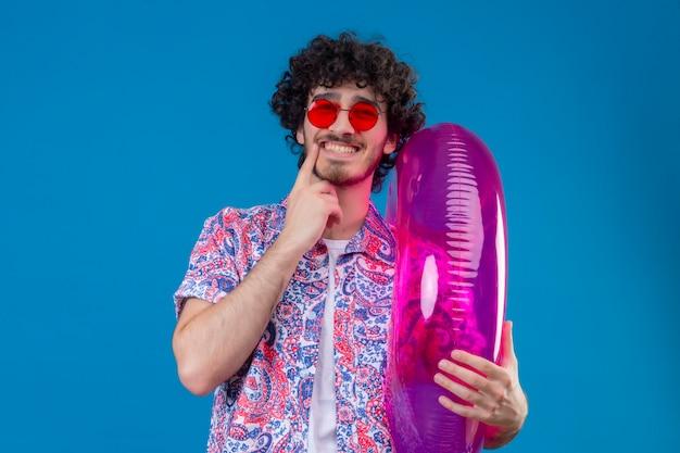 Uśmiechnięty młody przystojny mężczyzna kręcone w okularach przeciwsłonecznych, trzymając pierścień pływacki z palcem na brodzie na na białym tle niebieska ściana z miejsca na kopię