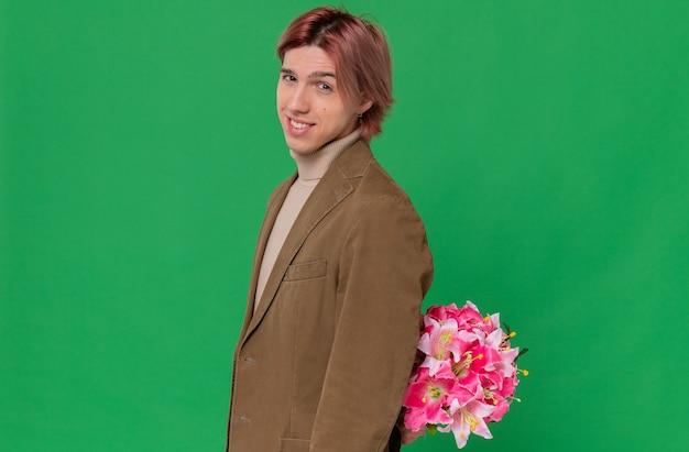 Uśmiechnięty młody przystojny mężczyzna stojący bokiem i trzymający bukiet kwiatów za plecami patrzący