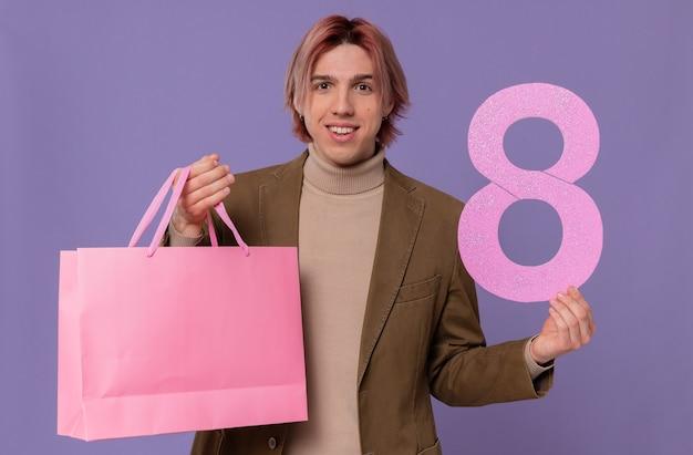 Uśmiechnięty młody przystojny mężczyzna trzyma różową torbę na prezent i numer osiem