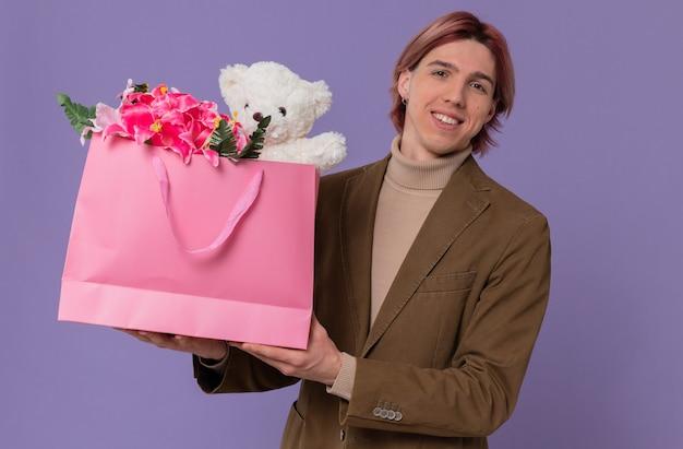 Uśmiechnięty młody przystojny mężczyzna trzyma różową torbę na prezent z kwiatami i misiem