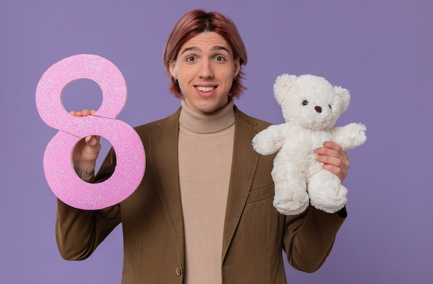 Uśmiechnięty młody przystojny mężczyzna trzyma różowy numer osiem i białego misia