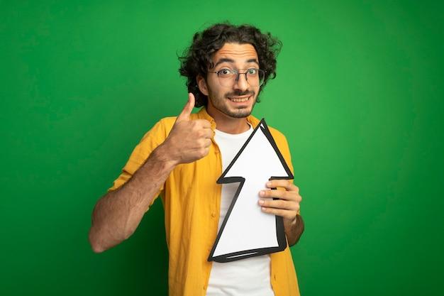 Uśmiechnięty młody przystojny mężczyzna w okularach trzyma znak strzałki, który jest skierowany w górę, patrząc na przód, pokazując kciuk w górę na białym tle na zielonej ścianie