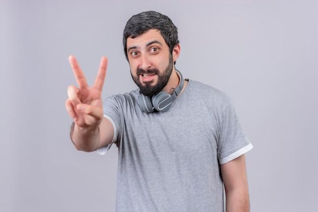 Uśmiechnięty młody przystojny mężczyzna w słuchawkach na szyi i robi znak pokoju na białym tle na białej ścianie
