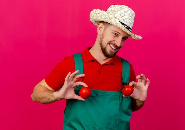 Uśmiechnięty młody przystojny ogrodnik słowiański w mundurze i kapeluszu, trzymając pomidory w pobliżu klatki piersiowej, patrząc