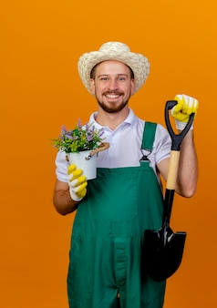 Uśmiechnięty młody przystojny ogrodnik słowiański w mundurze, w kapeluszu i rękawiczkach ogrodniczych, trzyma łopatę i doniczkę, patrząc odizolowany na pomarańczowej ścianie