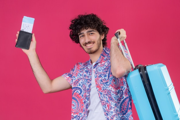 Uśmiechnięty młody przystojny podróżnik kręcone mężczyzna trzyma portfel i bilety lotnicze i walizkę na na białym tle różowej ścianie