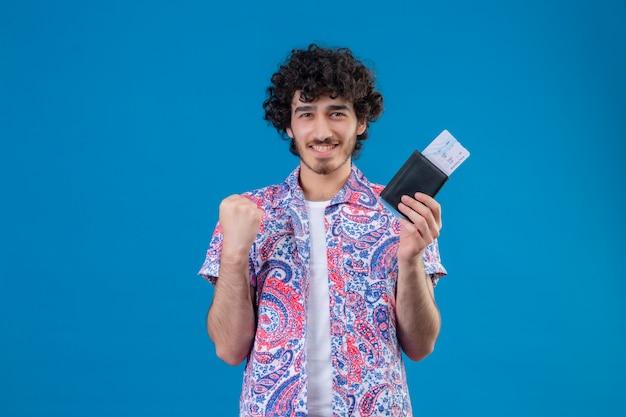 Uśmiechnięty młody przystojny podróżnik mężczyzna trzyma portfel i bilety lotnicze z podniesioną pięścią na odosobnionej niebieskiej ścianie z miejsca na kopię