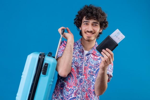 Uśmiechnięty młody przystojny podróżnik mężczyzna trzyma walizkę, bilety lotnicze i portfel na na białym tle niebieska ściana