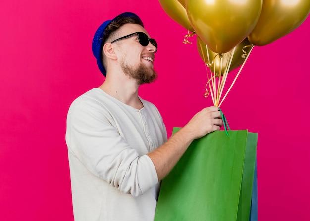 Uśmiechnięty młody przystojny słowiański imprezowicz w kapeluszu imprezowym i okularach przeciwsłonecznych stojący w widoku profilu, patrząc prosto trzymając balony i papierowe torby odizolowane na różowej ścianie