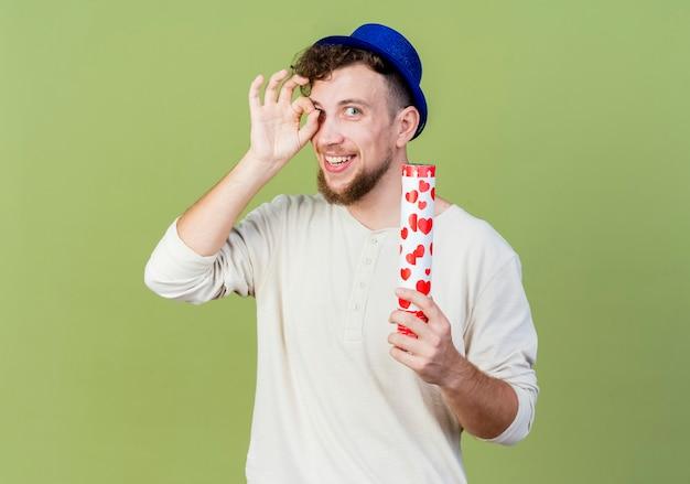 Uśmiechnięty młody przystojny słowiański imprezowicz w kapeluszu imprezowym, patrząc na kamery, robi gest spojrzenia, trzymając armatę konfetti na białym tle na oliwkowym tle z miejsca na kopię
