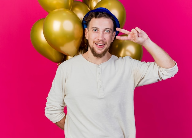 Uśmiechnięty młody przystojny słowiański imprezowicz w kapeluszu imprezowym, trzymając balony za plecami, robi znak pokoju patrząc na kamerę odizolowaną na szkarłatnym tle