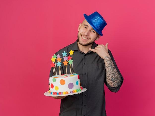 Uśmiechnięty młody przystojny słowiański imprezowicz w kapeluszu imprezowym, trzymając tort urodzinowy z gwiazdami, patrząc na kamerę, robi gest połączenia na białym tle na szkarłatnym tle z miejsca na kopię