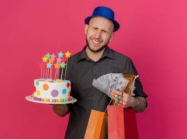 Uśmiechnięty młody przystojny słowiański imprezowicz w kapeluszu na przyjęcie trzymający tort urodzinowy pieniądze pakiet prezentów i papierowe torby z zamkniętymi oczami na białym tle na szkarłatnym tle z miejsca na kopię