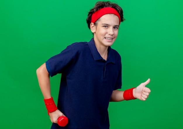 Uśmiechnięty młody przystojny sportowy chłopiec noszący opaskę i opaski na nadgarstek z aparatami ortodontycznymi trzymający hantle patrząc z przodu pokazujący kciuk w górę odizolowany na zielonej ścianie