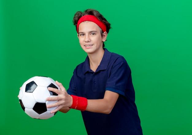 Uśmiechnięty młody przystojny sportowy chłopiec w opasce i opaskach na nadgarstek z aparatami ortodontycznymi wyciągającymi piłkę nożną odizolowaną na zielonej ścianie z miejscem na kopię