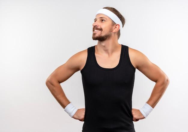 Uśmiechnięty młody przystojny sportowy mężczyzna nosi opaskę i opaski na rękę, patrząc na bok z rękami w talii na białym tle na białej przestrzeni