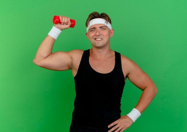 Uśmiechnięty młody przystojny sportowy mężczyzna nosi opaskę i opaski na rękę podnosząc hantle kładąc rękę na talii na białym tle na zielonej ścianie