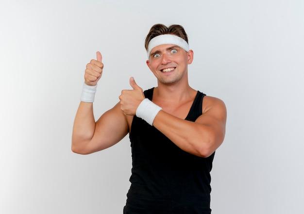 Uśmiechnięty młody przystojny sportowy mężczyzna nosi opaskę i opaski na rękę pokazując kciuki do góry na białym tle na białej ścianie
