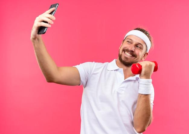 Uśmiechnięty młody przystojny sportowy mężczyzna nosi opaskę i opaski na rękę trzymając telefon komórkowy i hantle i patrząc na telefon na białym tle na różowej przestrzeni