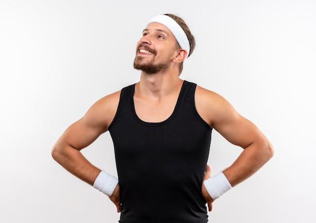Uśmiechnięty młody przystojny sportowy mężczyzna nosi opaskę i opaski na rękę z patrząc w górę rękami w talii na białym tle na białej przestrzeni
