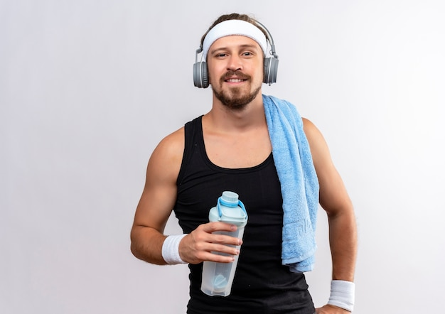 Uśmiechnięty młody przystojny sportowy mężczyzna nosi pałąk i opaski na rękę i słuchawki, trzymając butelkę wody z ręcznikiem na ramieniu na białym tle na białej przestrzeni