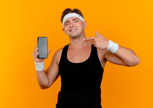 Uśmiechnięty młody przystojny sportowy mężczyzna nosi pałąk i opaski na rękę pokazując i wskazując na telefon komórkowy na białym tle na pomarańczowej ścianie
