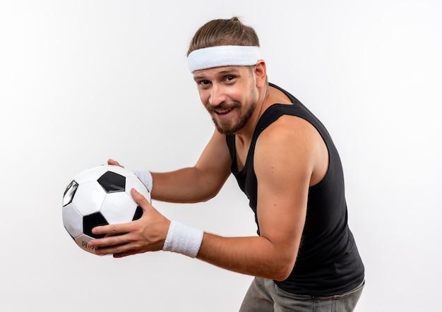 Uśmiechnięty młody przystojny sportowy mężczyzna nosi pałąk i opaski na rękę stojąc w widoku profilu trzymając piłkę nożną na białym tle na białej przestrzeni