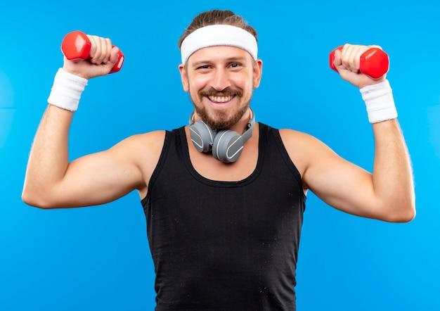 Uśmiechnięty młody przystojny sportowy mężczyzna nosi pałąk i opaski ze słuchawkami na szyi podnosząc hantle na białym tle na niebieskiej przestrzeni