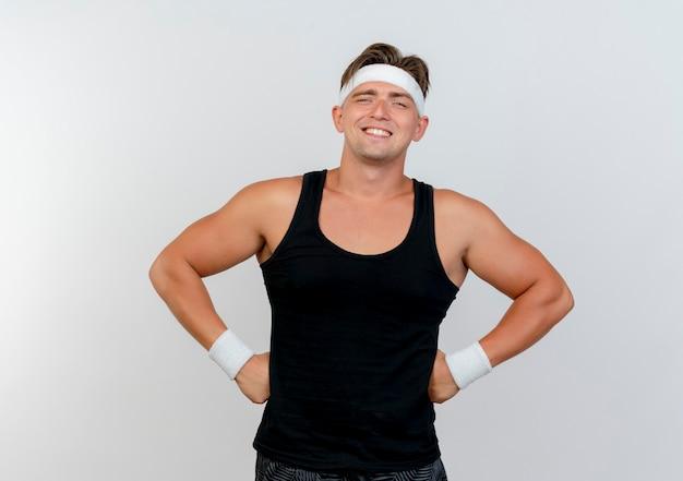 Uśmiechnięty młody przystojny sportowy mężczyzna noszenie opaski i opaski na rękę kładąc ręce na talii na białym tle na białej ścianie