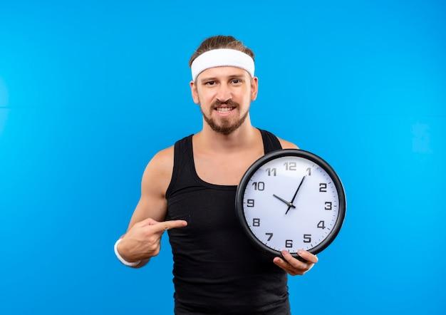 Uśmiechnięty młody przystojny sportowy mężczyzna noszenie opaski i opaski na rękę trzymając i wskazując na zegar na białym tle na niebieskiej przestrzeni