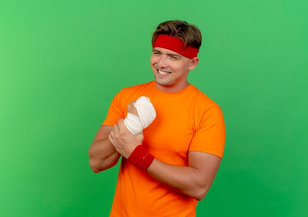 Uśmiechnięty młody przystojny sportowy mężczyzna ubrany w opaskę i opaski na rękę, trzymając jego ranny nadgarstek owinięty bandażem na białym tle na zielonej ścianie
