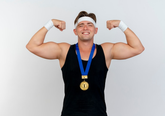 Uśmiechnięty młody przystojny sportowy mężczyzna ubrany w opaskę i opaski na rękę z medalem wokół szyi, gestykulując silny na białym tle na białej ścianie