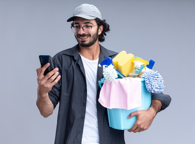 Uśmiechnięty młody przystojny sprzątacz sobie t-shirt i czapkę trzyma wiadro narzędzi do czyszczenia i patrząc na telefon w ręku na białym tle na białej ścianie