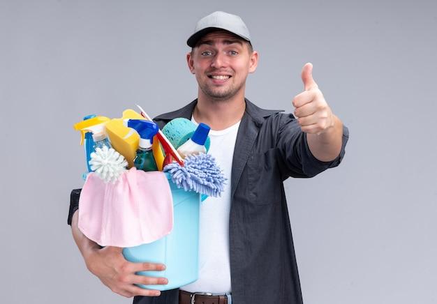 Uśmiechnięty młody przystojny sprzątacz sobie t-shirt i czapkę trzyma wiadro narzędzi do czyszczenia pokazując kciuk do góry na białym tle na białej ścianie