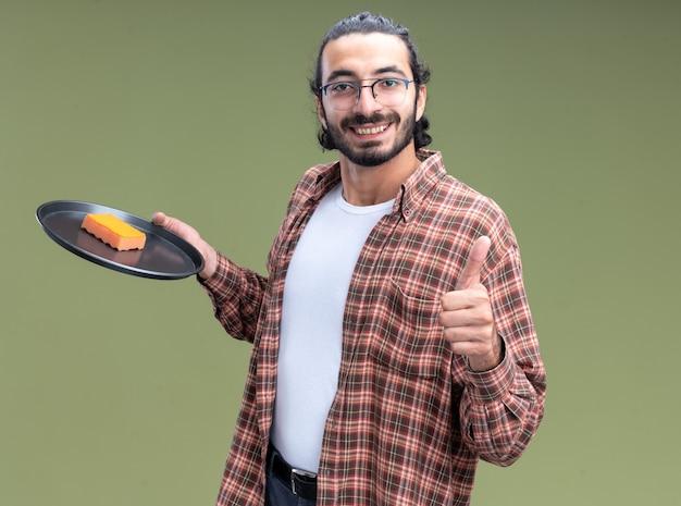 Uśmiechnięty młody przystojny sprzątacz sobie t-shirt, trzymając gąbkę na tacy, pokazując kciuk do góry na białym tle na oliwkowej ścianie