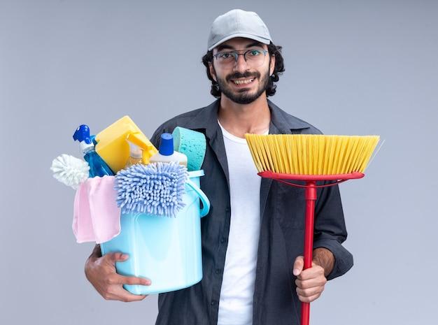 Uśmiechnięty młody przystojny sprzątacz ubrany w koszulkę i czapkę, trzymający wiadro z narzędziami do czyszczenia z mopem na białym tle na białej ścianie