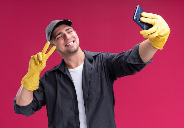 Uśmiechnięty młody przystojny sprzątacz ubrany w koszulkę i czapkę w rękawiczkach bierze selfie pokazujące gest pokoju na różowej ścianie