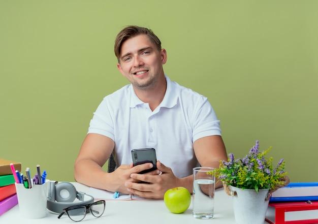 Uśmiechnięty młody przystojny student płci męskiej siedzi przy biurku z narzędzi szkolnych trzymając telefon na oliwkowej zieleni