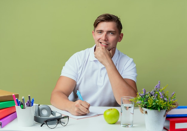 Uśmiechnięty młody przystojny student płci męskiej siedzi przy biurku z narzędziami szkolnymi, kładąc rękę na brodzie i pisze coś na notebooku na oliwkowej zieleni